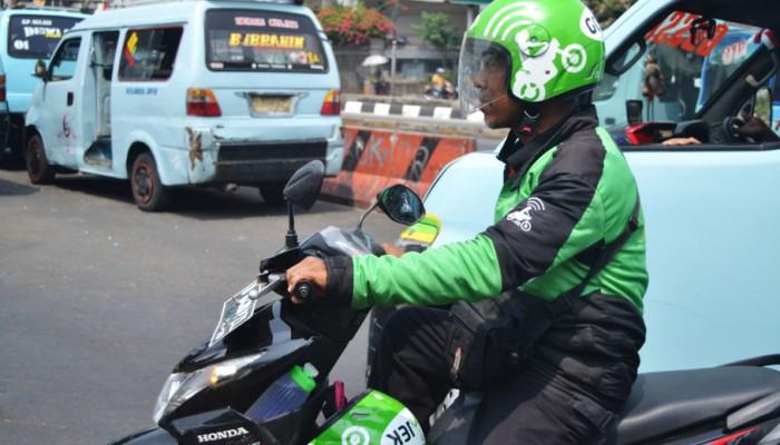 Seorang go-jek sedang menunggu penumpangnya di Terminal Senen, 18 Agustus 2015. Transportasi umum semakin mudah kita gunakan dengan adanya go-jek di Jakarta dan sekitarnya. Go-jek mampu membantu pramudi go-jek dalam bidang ekonomi dan pelanggan dalam mengatasi kemacetan agar sampai di tujuan lebih cepat. (JG Photo/ Sheryl Yehovia)